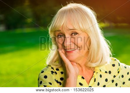 Portrait of smiling senior female. Woman resting cheek on hand. Hopes and joys. The best is still ahead.