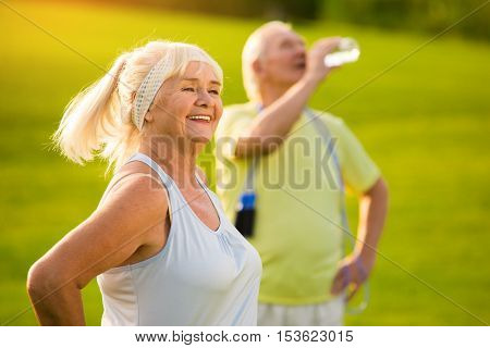 Senior woman smiling outdoors. Elderly lady with cheerful face. Get in shape for summer. Build effective program of trainings.
