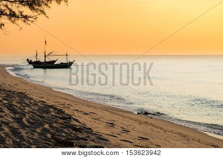 Beautiful sunset and beach with fishing boat, Thailand.