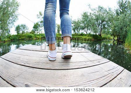 Woman legs on wooden pier. Beautiful landscape