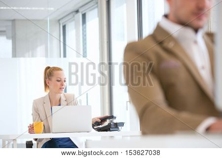 Young businessman using telephone with male colleague in foreground at office