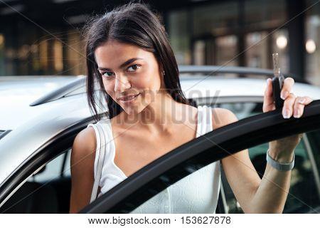 Closeup of beautiful young woman standing near opened car outdoors