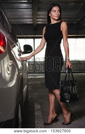Happy young businesswoman standing and opening the door of her car on parking
