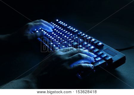 illuminated keyboard. male hands typing on a computer. hacker or programmer at work. on a black background.