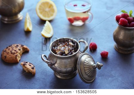 Metal pot with brown sugar and tea on table