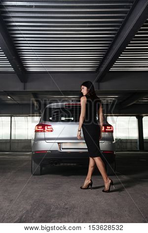 Back view of attractive young businesswoman walking to her car on parking