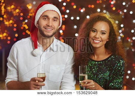 Young man and woman with glasses of champagne at Christmas party