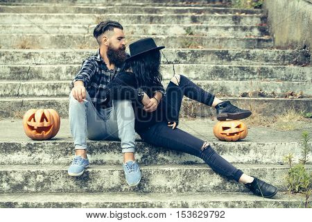 young halloween couple of bearded man smoking cigarette with beard and mustache and girl in black witch hat on stony stairs with traditional autumn holiday symbol of orange spooky pumpkin outdoor