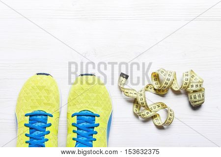 Flat lay shot of Sport equipment. Sneakers water earphones and phone on wooden background. Focus is only on the sneakers.