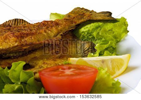 Fried Fish flounder on white plate with lettuce tomato and lemon isolated