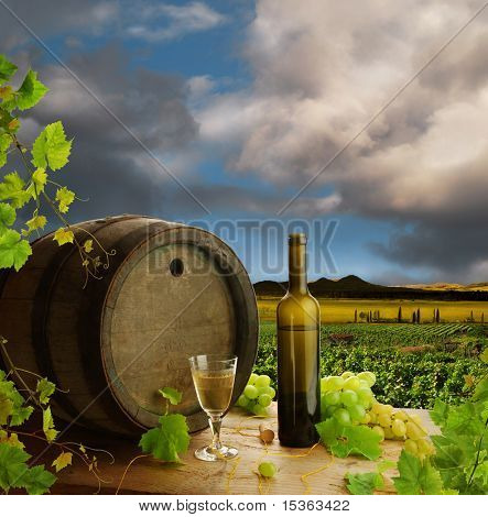 White wine with old wine barrel on background of vineyard landscape