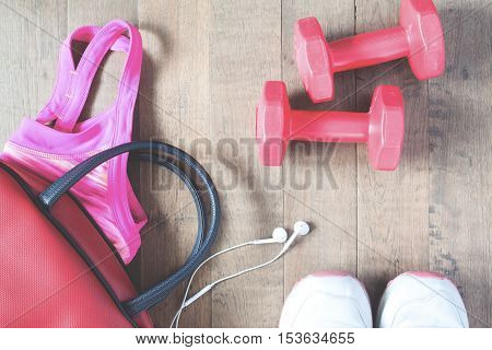 Flat lay of fitness equipments on wooden floor with vintage color effect top view