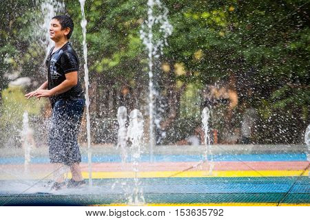 Tblisi Georgia - August 15 2016: Color image of a child cooling off playing in a public fountain in Tbilisi Georgia.