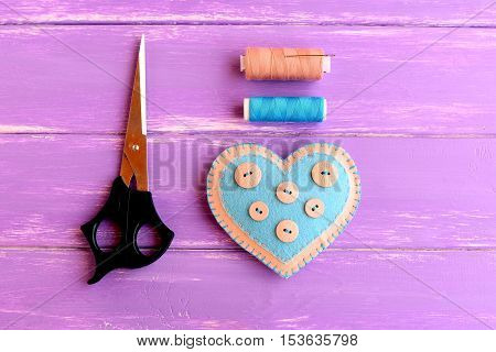 How to create a felt heart crafts. Step. Decorative felt heart with buttons, scissors, thread set, needle on wooden background. Sewing crafts for Valentine's day, wedding, mother's day