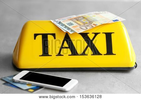 Yellow taxi roof sign with phone, credit cards and Euro banknotes on gray background, closeup