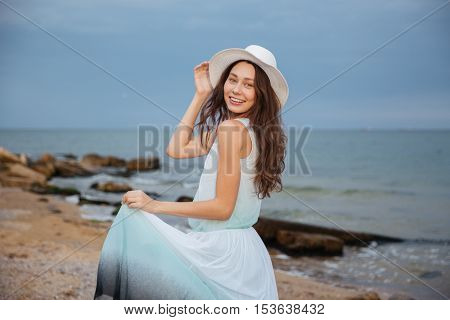 Happy attractive young woman in hat walking on the beach