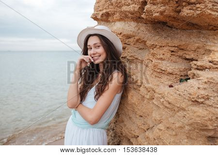 Portrait of cheerful cute girl standing near the rock on the beach