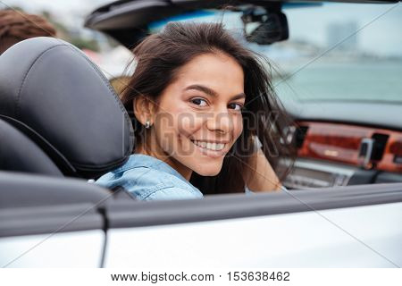 Smiling young woman sitting inside her convertible car on beach