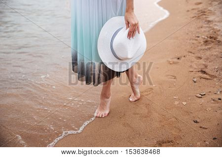 Closeup of legs of young woman in dress holding hat and walking barefoot on the beach