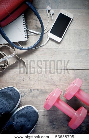 Flat lay of cellphone and sport equipment on wooden background. Sport wear Sport fashion Sport accessories Sport equipment copy space top view with vintage filter