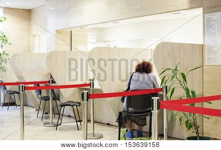 A patient female is sitting with his back to the camera on a reception or an information center in a hospital.