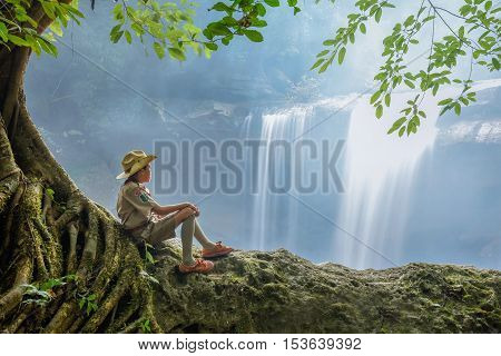 Boy scout sits alone in water fall
