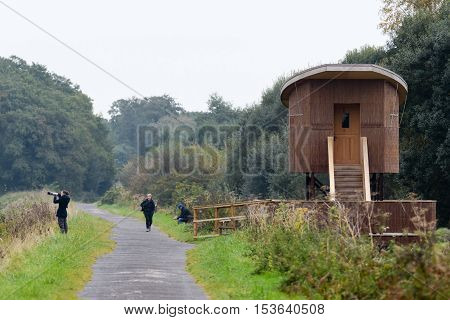 SHAPWICK HEATH, UK - OCTOBER 25 2016  Bird hide and photographer at Shapwick Heath National Nature Reserve. New hide on the Avalon Marshes in the Somerset Levels