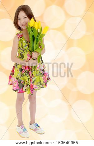 Adorable little Caucasian girl in summer dress holding a bouquet of yellow tulips.Brown festive, Christmas background with white snowflakes, circles.