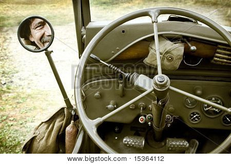 Close up of vintage jeep Willys with man face in mirror