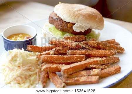 Vegetable burger with sweet potato fries served on a white plate