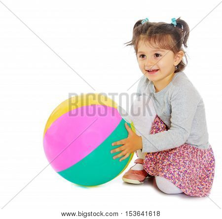 Cute little dark-haired girl with short pigtails on the head, hugging his big , inflatable, striped, vinyl ball.Isolated on white background.
