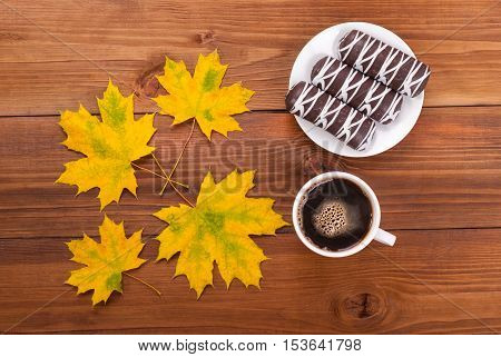 Coffee cakes autumn leaves on the wooden background.