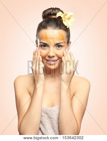 Young woman applying scrub on face against color background. Skin care concept.
