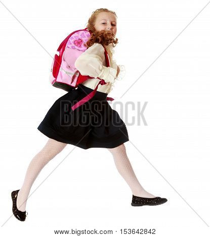 Pretty little girl schoolgirl in white blouse and black skirt to hurry to school. She jumps over the obstacle.Isolated on white background.