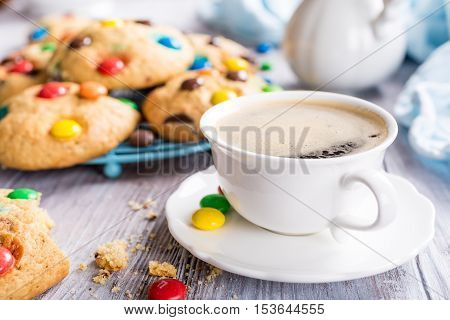 Cup coffee with homemade cookies with colorful chocolate candies on old white wooden table.