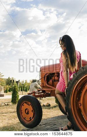 young girl in a pink dress with polka dots near the tractor background.