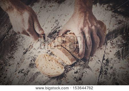 Baking and cooking concept background. Hands of baker cutting bread loaf with knife on rustic wooden table sprinkled with flour. Stained dirty hands of baker