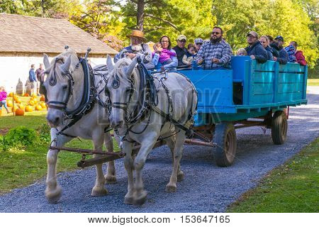 Lancaster PA USA - October 9 2016: Visitors ride in an old horse-drawn farm wagon at the Landis Valley Farm and Museum during the annual Harvest Day event.