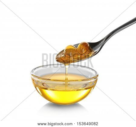 Spoon with gelatin capsules and glass bowl of cod liver oil on white background