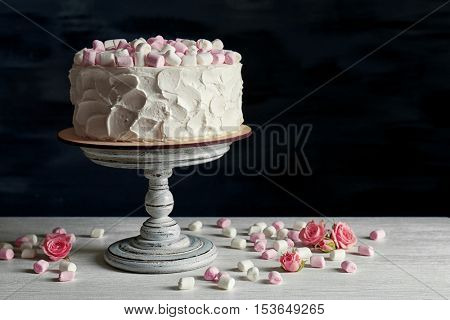 Delicious cake with marshmallows on wooden table