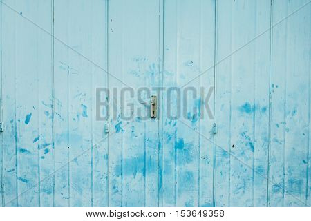 The vintage folding metal door with light blue painted and hand print stain