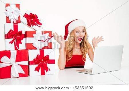 Cheerful excited young woman in samta claus hat sitting and using laptopx over white background