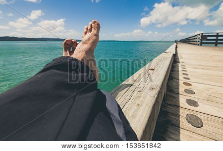 Man relaxing at cornwallis wharf, Auckland, New Zealand.
