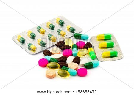 Pile of different pills and capsule of medicine on white background