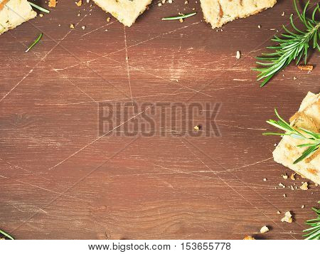 Dark wooden background with winter cookies with rosemary herb and pine and pistachio nuts decorated with rosemary sprigs