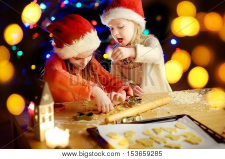 Two adorable little sisters baking Christmas cookies by a fireplace on Christmas eve