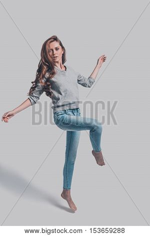 Beauty in motion. Full length studio shot of attractive young woman in casual wear standing on one leg and stretching out hands