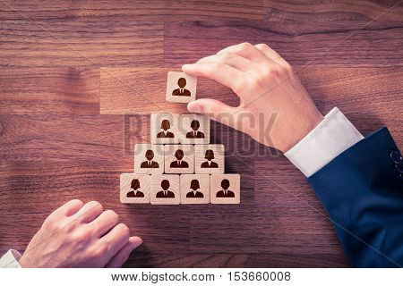 Human resources and corporate hierarchy concept - recruiter complete team by one leader person (CEO) represented by icon.