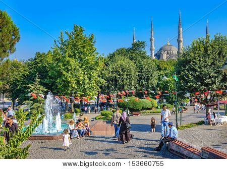 Istanbul Turkey - July 27 2011: View of a park full of people admiring majestic fountain and blue mosque behind it in Istanbul.