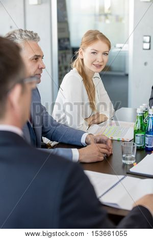 Portrait of young businesswoman sitting with male colleagues in conference room